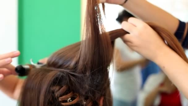 Hair stylist combing hair of woman
