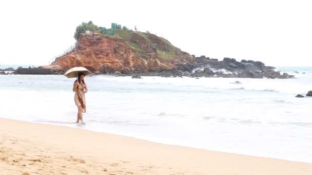 Japanischer Tourist spaziert mit Sonnenschirm am Strand