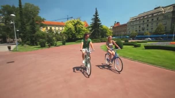 Mladý pár, jízda na kole přes park