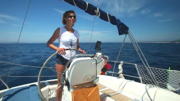 Woman at wheel steering sailboat