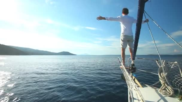 Man standing on bow of sailing boat