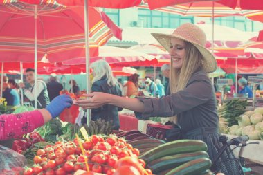 Attractive blonde woman with straw hat paying vegetables on  marketplace.
