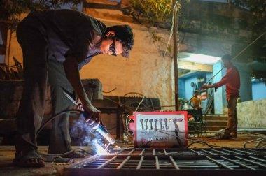 Indian worker welding metal parts