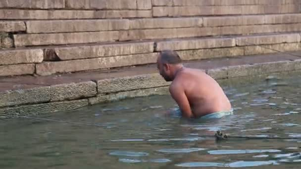 99f6344f21a Indian man bathing at Ganges river in Varanasi. — Stock Video ...