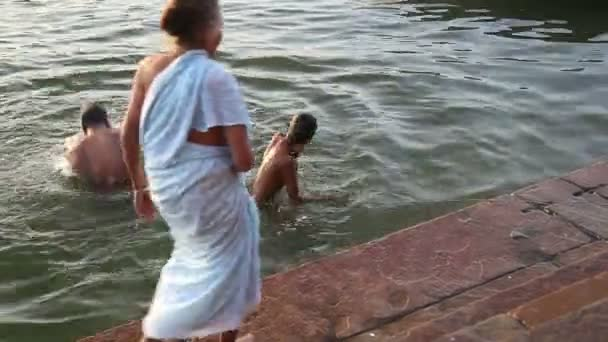 4c05cf33c7e Man and boy bathing in Ganges, with woman approaching water.– stock footage
