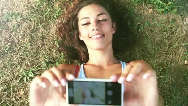Tři mladí dospělí s selfie, ležící na trávě