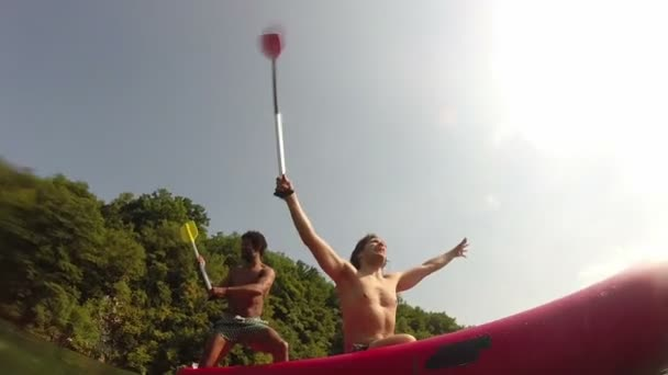 Two male friends having fun waving with paddles in a canoe