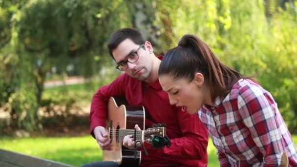 Člověk hraje kytaru, zatímco žena zpívá