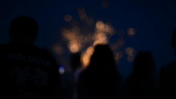 Skupina lidí zůstane před ohňostroj a fotografie světelné show