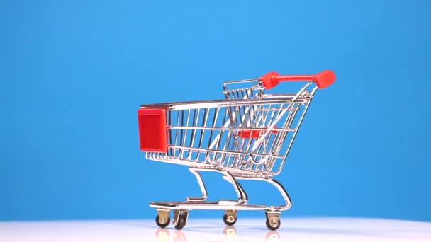 Shopping trolley on blue background