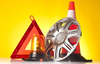 Road emergency items and car accessories on yellow background