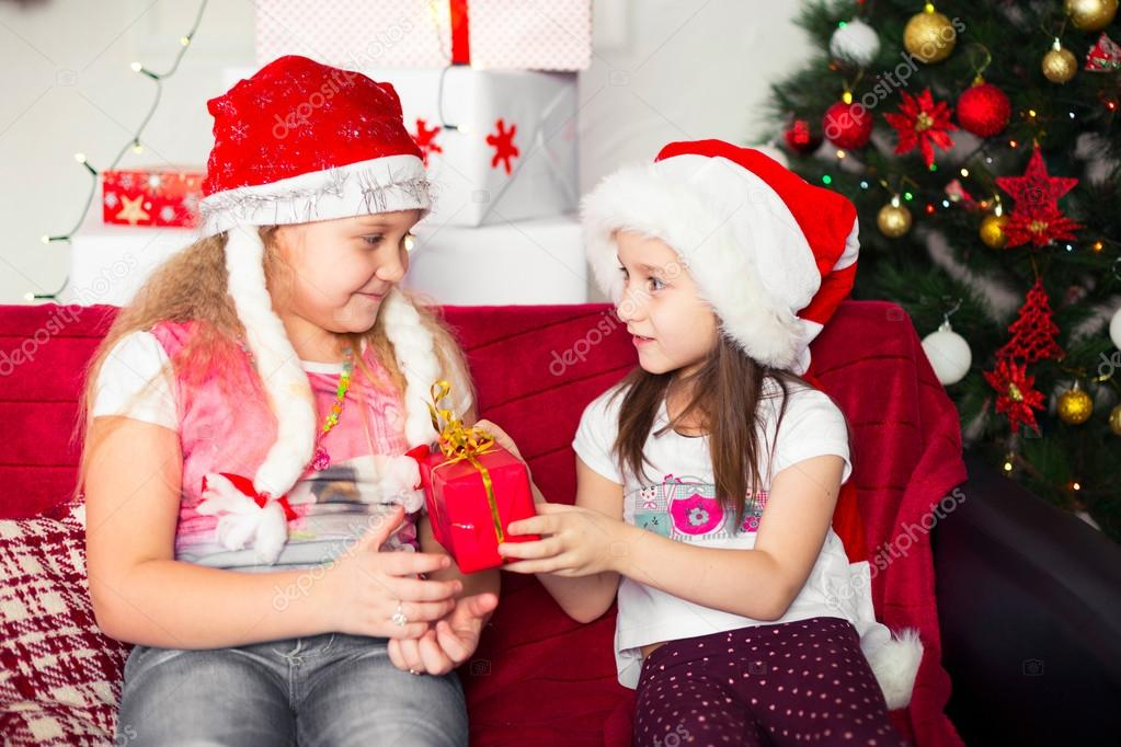 Two Girls In Christmas Costumes Sitting On The Couch Give Each Other