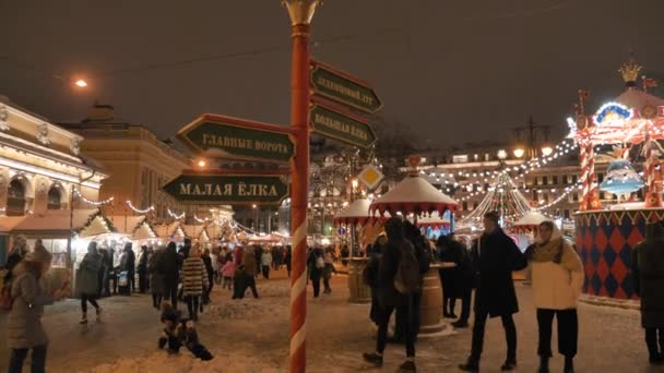 Crowds of people walk at the new years Christmas market in the city center along the stalls with Souvenirs and street food, buy gifts for the new year. RUSSIA, ST. PETERSBURG, DECEMBER 26, 2020