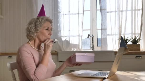 Glückliche Rentnerin bläst Geburtstagspapierpfeife gegen Laptop