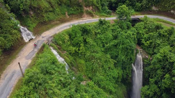 Motocykl cestovatel jízdy na malé silnici s vodopády a zelení.
