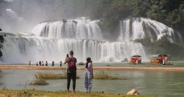 Turisté stojící u vodopádu Pan Gioc na vietnamské straně hranice