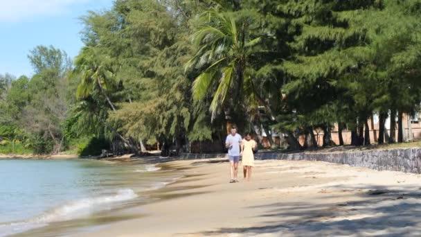 Šťastné a romantické mezirasové páry drží ruku a chodí po pláži.