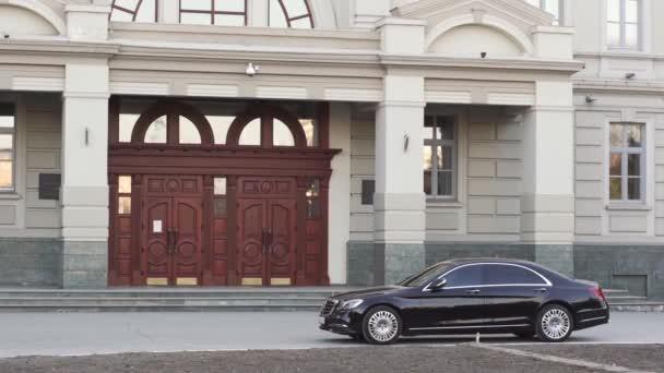 Schwarzes, teures Auto steht am Regierungsgebäude.