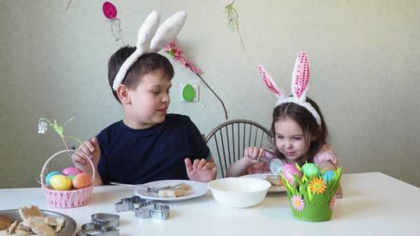 chlapec a dívka připravují koláčky na Velikonoce, smějí se. Bavte se na velikonočním lovu. Chlapec a dívka nosí králičí uši a malují vajíčka. barevná vejce.