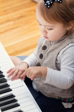 Toddler girl playing piano