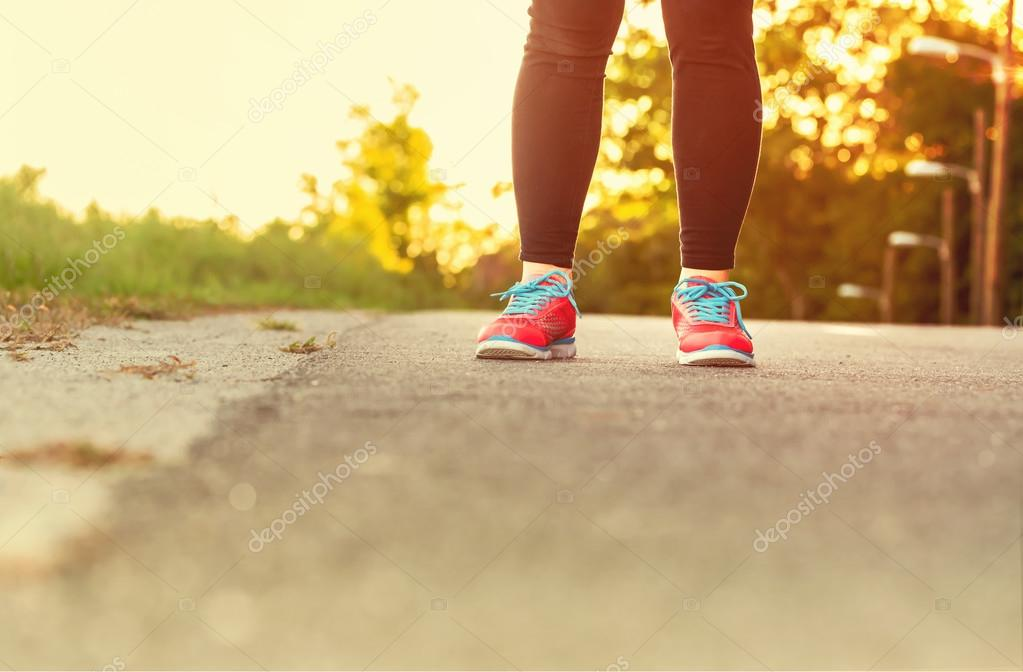 Фотообои Female athlete in running shoes ready for a run on a forest path
