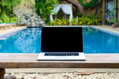 Vacation work with laptop on bench at pool