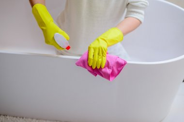 Female hands with yellow rubber gloves cleaning bath