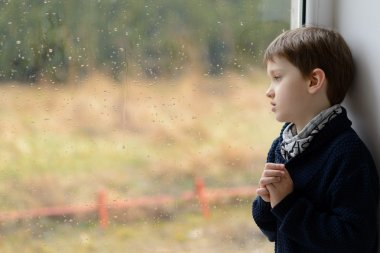 thoughtful little boy looking through the window.