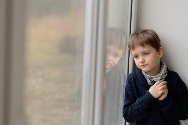 Sad thoughtful little boy looking through the window.
