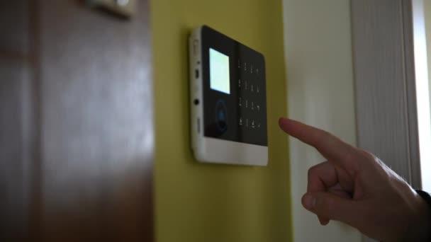 Detailní záběr rukou zadávajících bezpečnostní kód do poplašného systému.