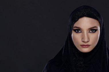 Close portrait of a beautiful Muslim woman dressed in black hijab