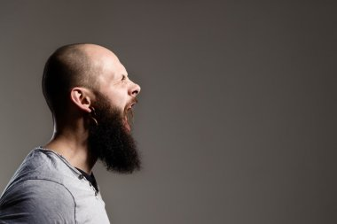 Side view portrait of screaming bearded man