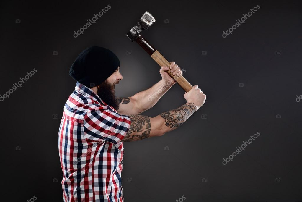 Furious lumberjack man swinging his axe