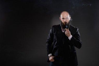 Bearded bald elegant man smoking a pipe