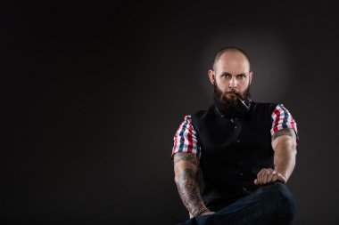 The bearded man in a vest and checkered shirt