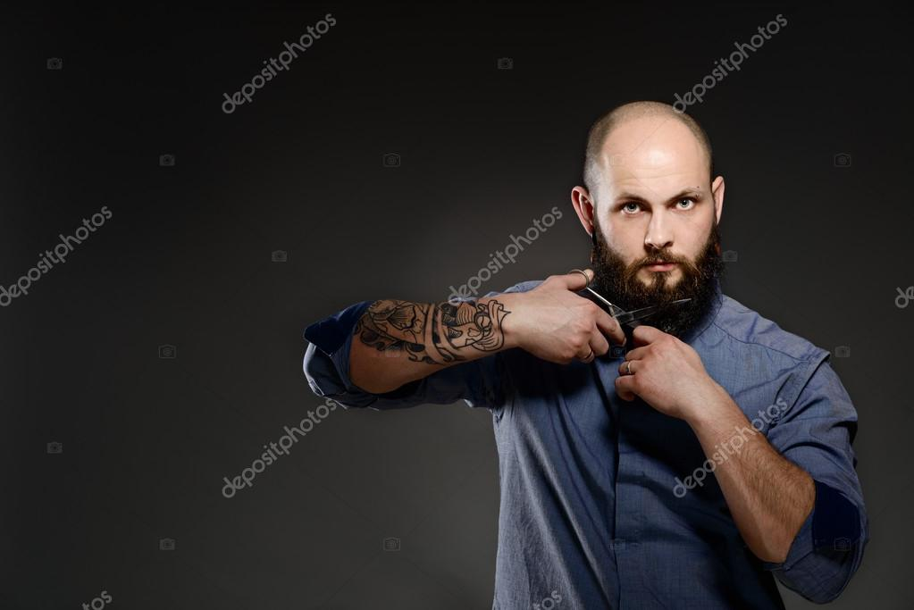 Portrait of a bearded man cutting his beard with scissors