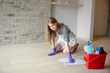 Nervous and tired beautiful young woman washes the floor on her knees