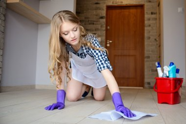 Beautiful young woman washes the floor on her knees.