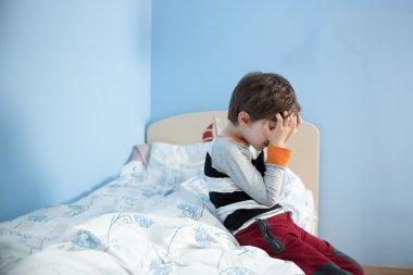 Sad, upset little boy sitting on the edge of his bed.