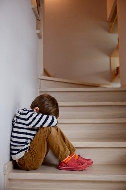 Sad little boy crying depressed sitting