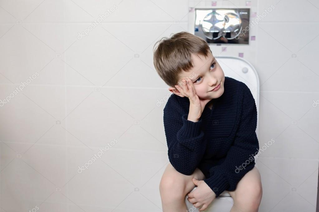 Thinking 6 year old boy sitting on the toilet.