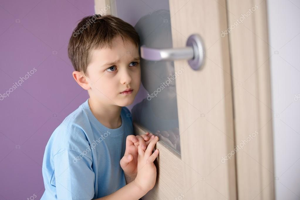 Sad, frightened child listening to a parent talking through the door