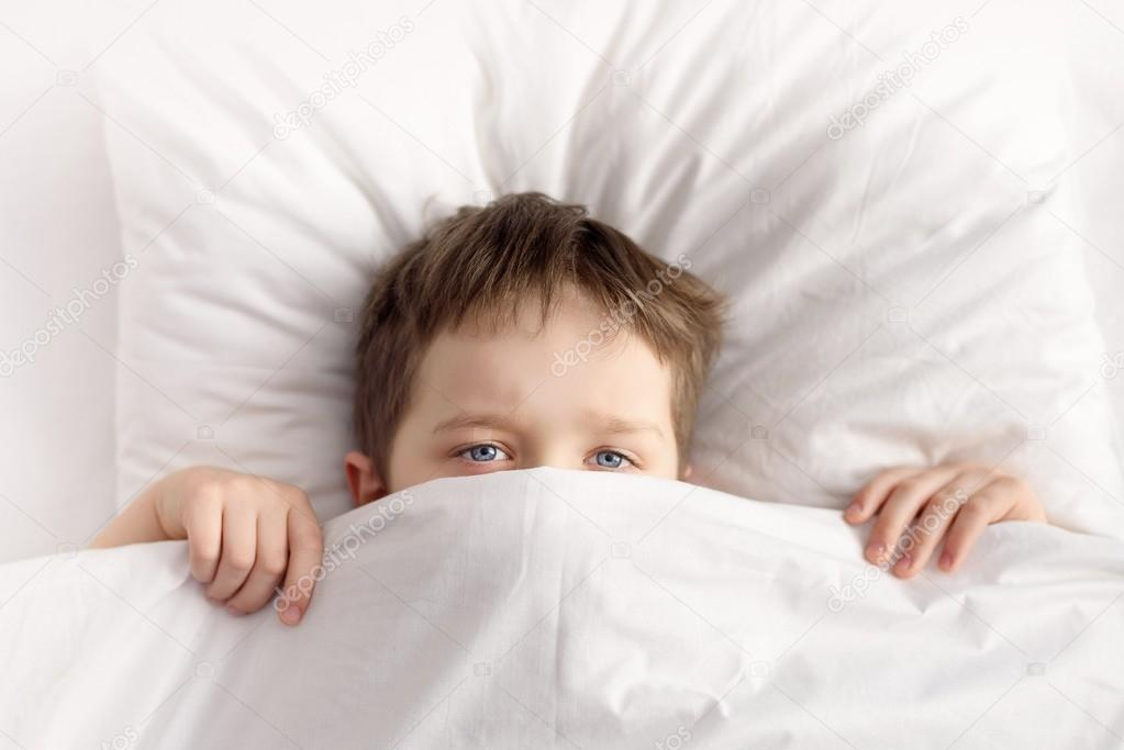 Little boy hiding in bed under the blanket at home