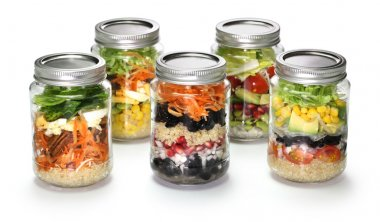 Salad in glass jar on white background