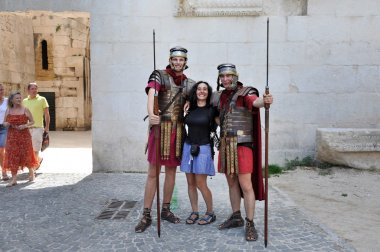 Men dressed as Roman soldiers posing with tourist
