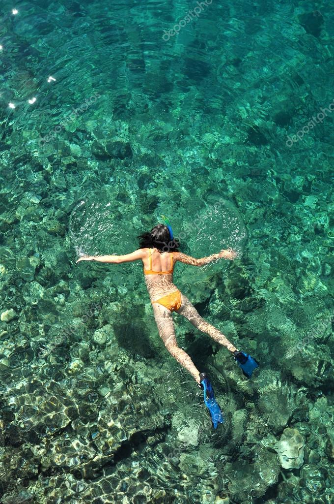 Young woman in swimsuit snorkeling in clear shallow tropical sea