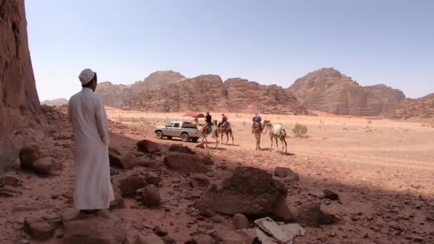 WADI RUM, JORDAN  MAY 19, 2018: Local Bedouin tourist guy relaxing in the shadow while  group of travelers taking a camel ride in the desert