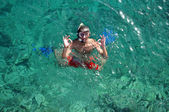 Fotografie Man with mask snorkeling and doing ok sign