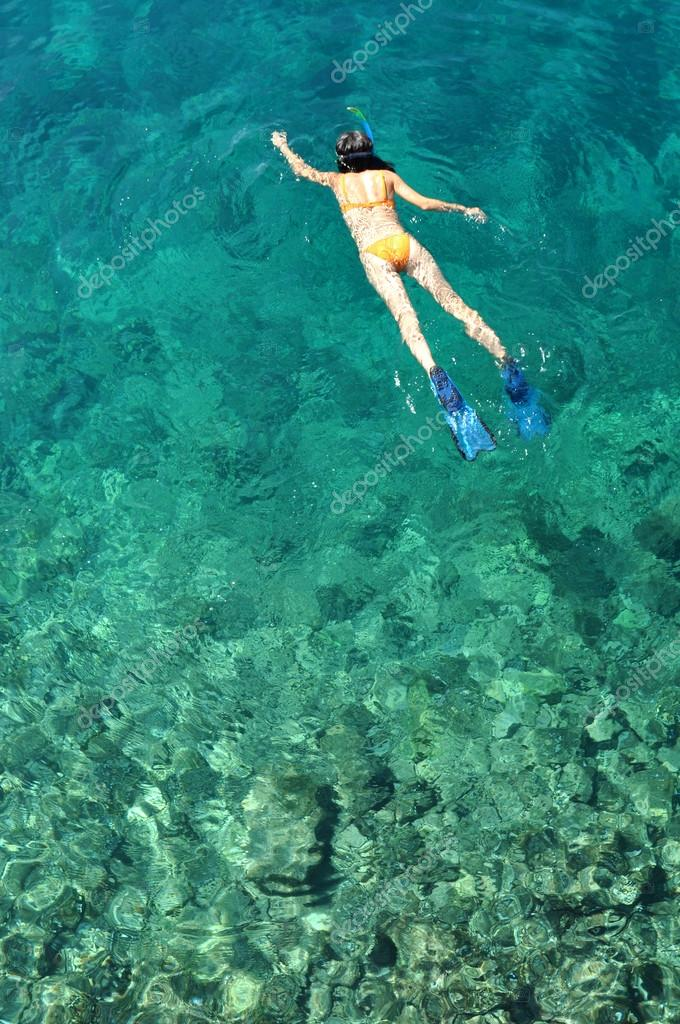 Young woman snorkeling in tropical sea
