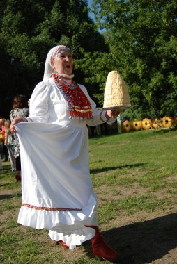 Woman in traditional dress carries chak-chak sweets at Sabantui celebration in Moscow